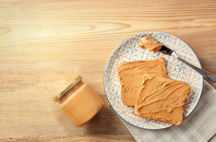 peanut butter on toast on patterned plate on wood table