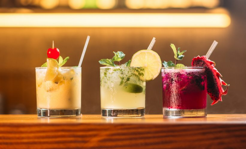 colorful cocktails with straws on bar