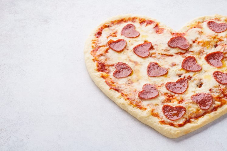 heart shaped pepperoni pizza on white background
