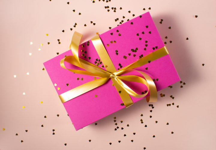 gift wrapped in pink paper with gold ribbon and glitter