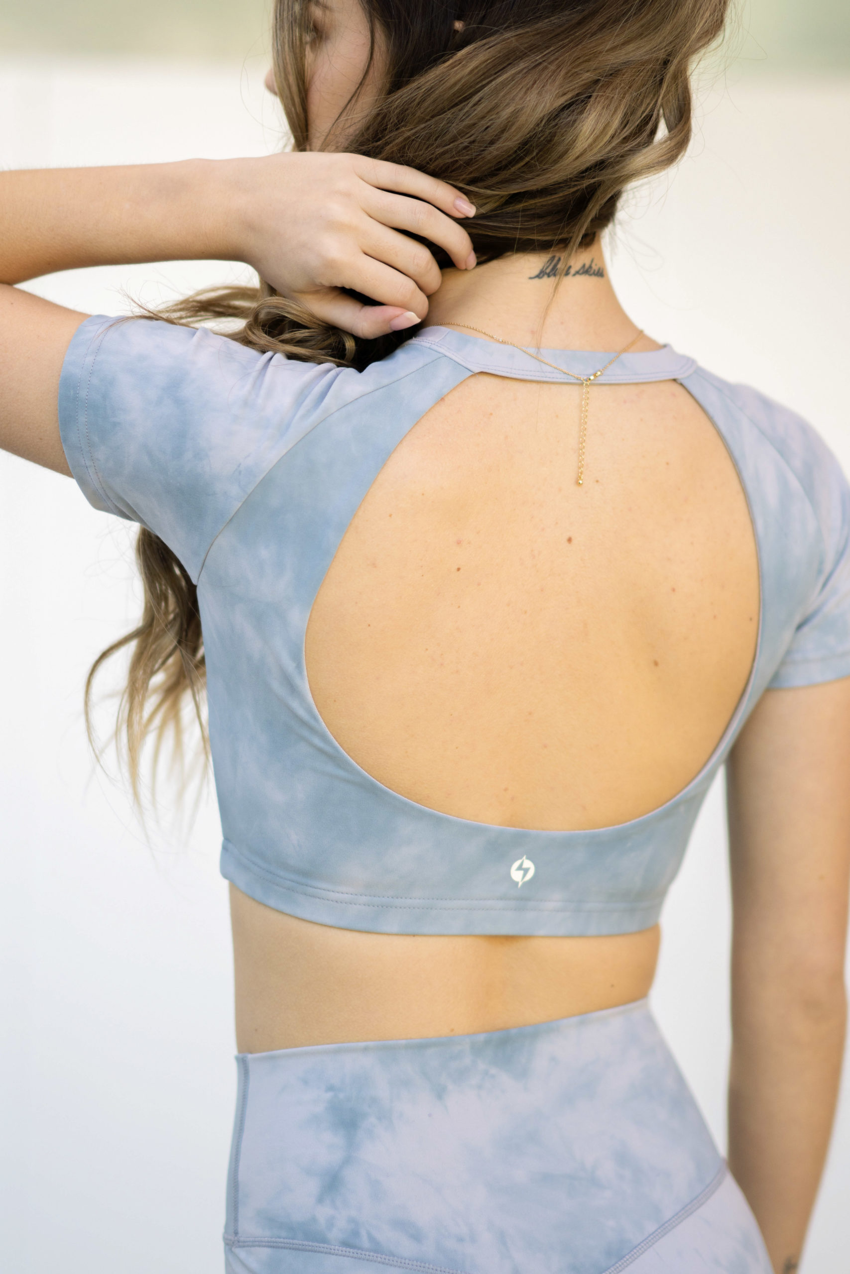 model wearing popflex marble collection baby bliss tee open back sky marble