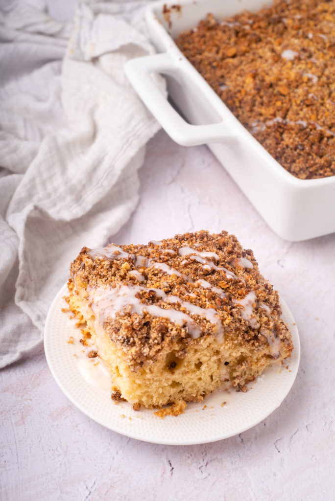 slice of gluten and dairy free cinnamon coffee cake with streusel and sugar free glaze on white plate with whole cake in background