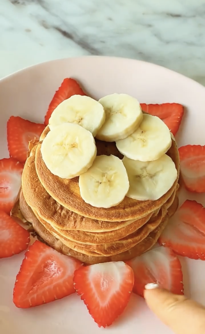stack of high protein pancakes with bananas and strawberries