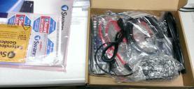 Foto del contenido de la caja. Viene un control remoto y sus pilas, tornillos, cables SATA.