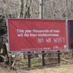 "Sign: ""This year thousands of men will die from stubbornness."" Grafitti: ""NO WE WON'T"""