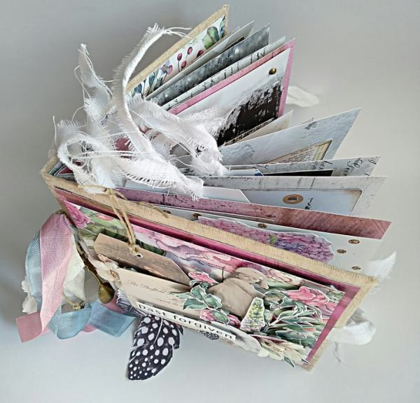 Romantyczny junk journal z widocznymi nad okładką paskami materiału.