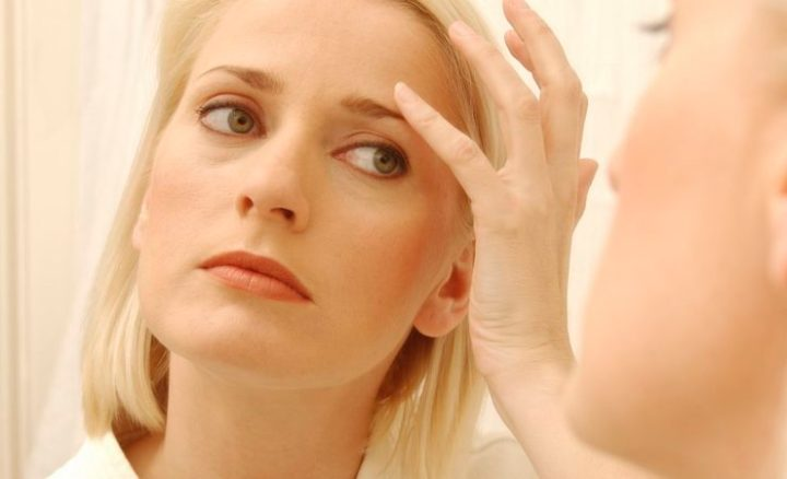 Woman checking herself for wrinkles in mirror
