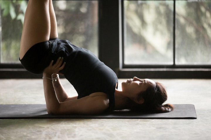 Young attractive woman practicing yoga at home, standing in Viparita Karani exercise, shoulderstand pose, working out wearing sportswear, black shorts and top, indoor close up image, studio background