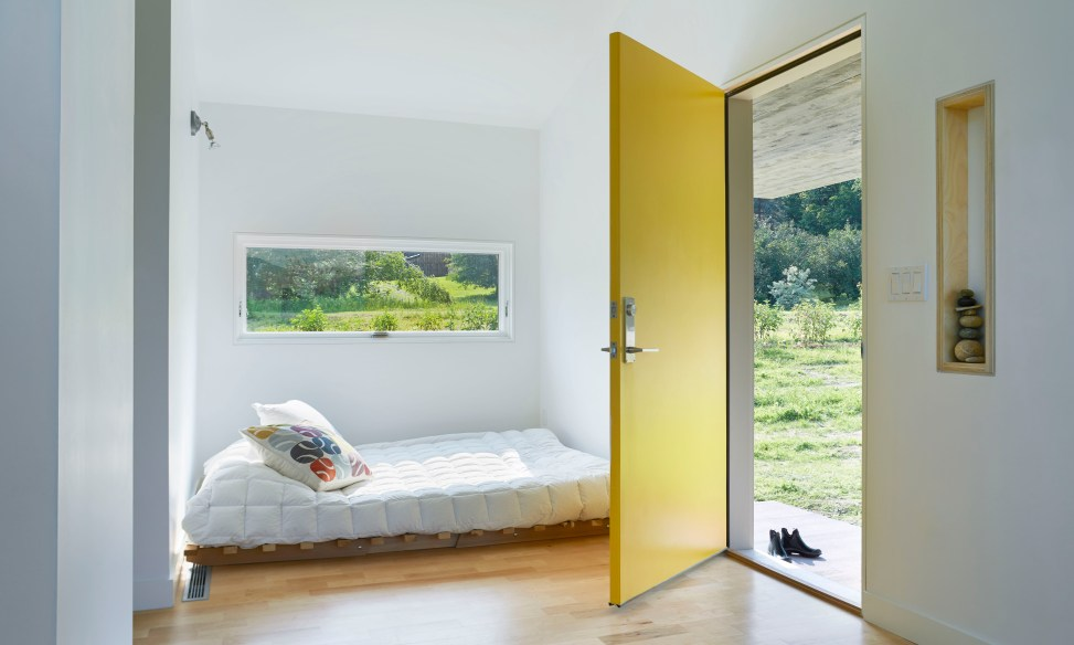 Entrance to tiny home with yellow door and Marvin window