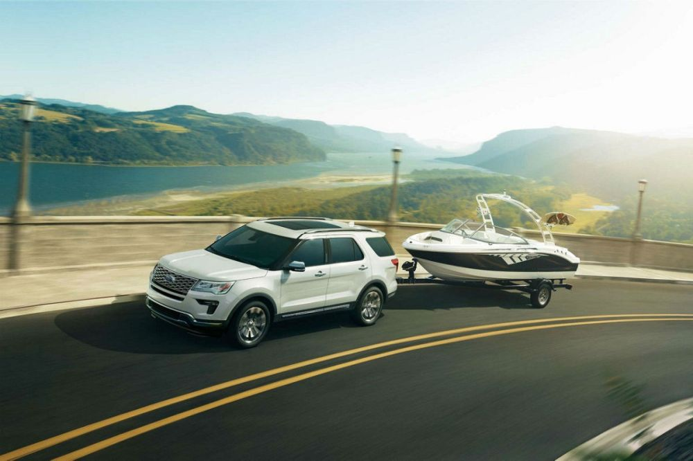 medium resolution of  white 2018 ford explorer towing a boat along a coastal highway
