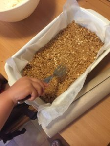 pressing down the oat mix into the baking tray