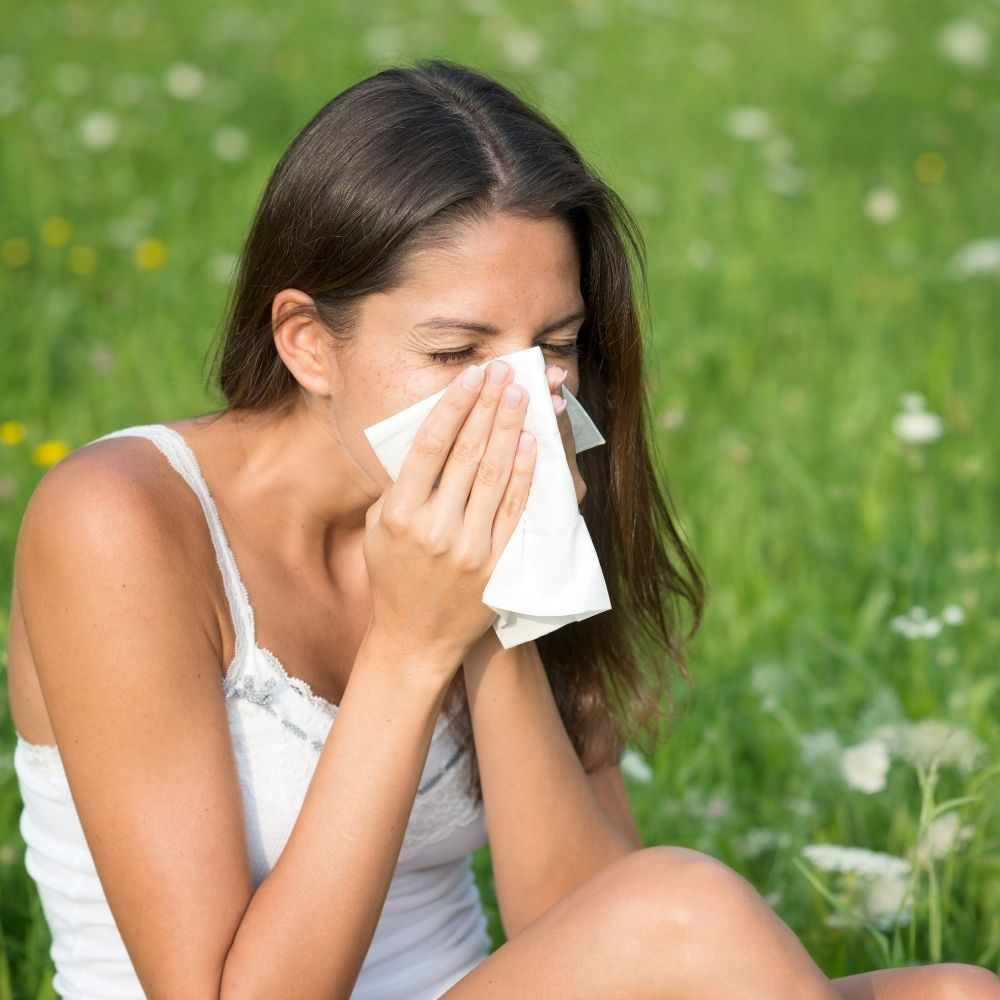 Woman sneezing with tissue