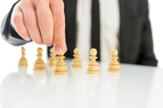 Closeup of businessman arranging chess figures pawns. Concept of human resources.