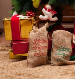 Gifts under the tree, red and gold, with ties. There are also two bags of coal. It is the night of the magi. The day 6 of January