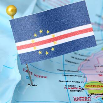 Cape Verdean paper flag over cheap plastic map. Shallow depth of field