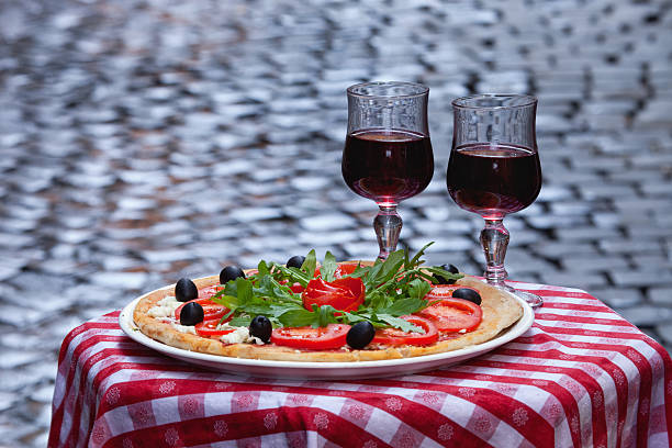 A fresh Pizza and 2 glasses of Red wine are displayed on a table in the old part of Rome with blurred cobblestones in the background