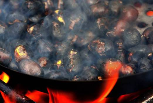 Chestnuts in a roasting pan over the fire during the Chestnut Festival in Feldthurns, Trentino-Alto Adige, Italy.