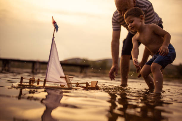 Grandfather and grandson playing with a sailboat toy on the lake