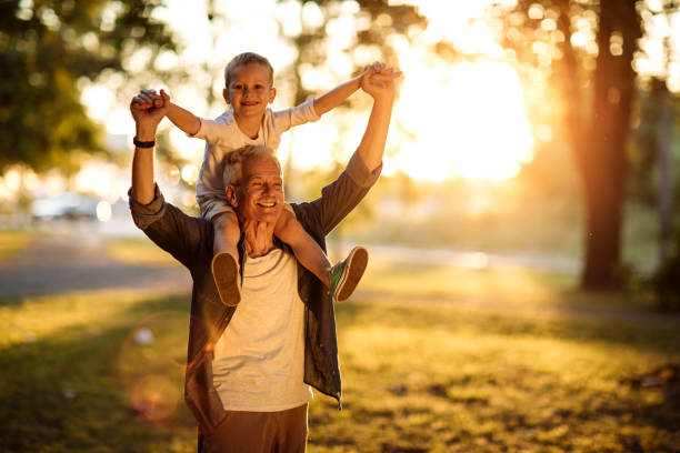 Happy grandpa carrying his cheerful grandson on the shoulders in the sunny park