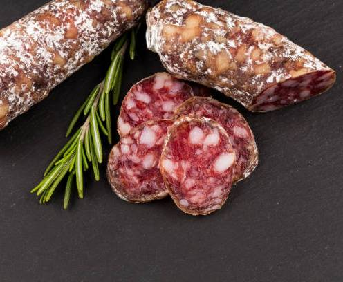 slices of salami on a dark stone board as a background