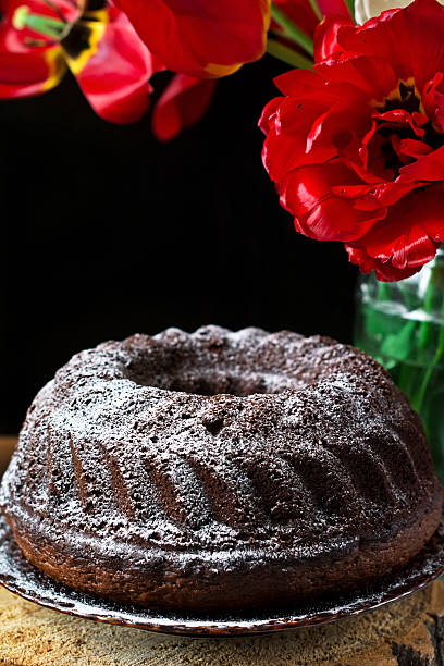 Chocolate bundt cake on plate on black background and red tulips above.