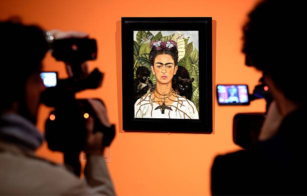 "Cameramen film the ""Self-portrait with with Thorn Necklace and Hummingbird"" by Mexican artist Frida Kahlo during an exhibition in Rome's Scuderie del Quirinale on March 18, 2014. The Scuderie del Quirinale host a exhibition on the life and work of Mexican artist Frida Kahlo (1907-1954), a symbol of the artistic avant-garde and exuberance of Mexican culture in the 20th century. The exhibition will run from March 20 until August 31, 2014. AFP PHOTO / ALBERTO PIZZOLI RESTRICTED TO EDITORIAL USE, MANDATORY CREDIT OF THE ARTIST, TO ILLUSTRATE THE EVENT AS SPECIFIED IN THE CAPTION (Photo credit should read ALBERTO PIZZOLI/AFP via Getty Images)"