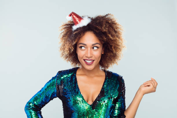 Portrait of excited young woman wearing green sequined dress and santa hat on white background.