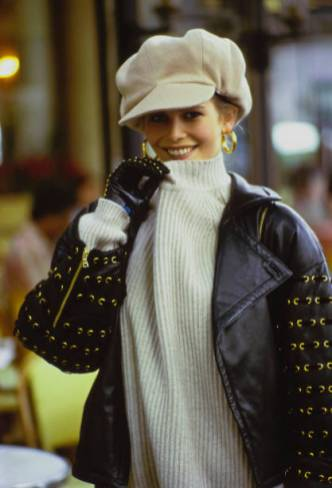 Vogue, September 1992 - Close up of model Claudia Schiffer on the street in Paris, France, in front of the Deux Magots Cafe, her right hand reaching up to tug on her sweater collar. She is wearing a black leather jacket with gold grommets and zippers by Valentino and an off-white TSE ribbed knit cashmere sweater. Accessories: gold studded black leather Renaud Pellegrino gloves; cream cap by Patricia Underwood for Marc Jacobs/Perry Ellis; gold hoop earrings by Napier. Hair by Serge Normant for Oribe at Elizabeth Arden. Makeup by Sonia Kashuk for Aveda. (Arthur Elgort/Conde Nast via Getty Images)