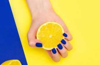 bright blue shiny creative manicure on yellow background. Women's hands through a torn sheet of paper.