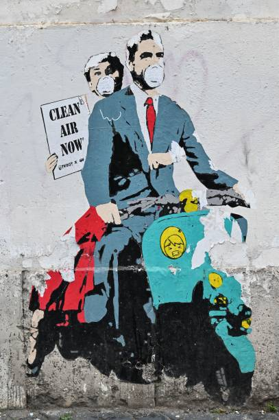 "A mural by street artist ""TV Boy"" depicting a famous film ""Roman Holiday"" with Gregory Peck and Audrey Hepburn as she holding a banner reading ""Clear Air Now"" is displayed on a wall near ancient Colosseum, in central Rome on March 14, 2020, during the COVID-19 outbreak caused by the novel coronavirus. (Photo by Andreas SOLARO / AFP) (Photo by ANDREAS SOLARO/AFP via Getty Images)"