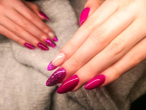 Close up of Fake Nails, Acrylic Nails, Gel nails on a woman's hand in neon colours