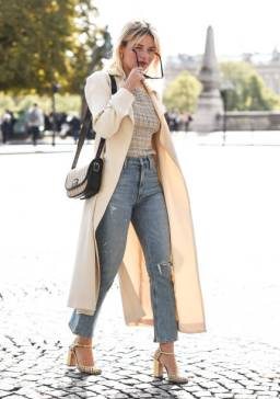 PARIS, FRANCE - SEPTEMBER 30: Camille Charriere is seen wearing a cream coat, plaid top and blue jeans and YSL bag outside the Sacai show during Paris Fashion Week SS20 on September 30, 2019 in Paris, France. (Photo by Daniel Zuchnik/Getty Images)
