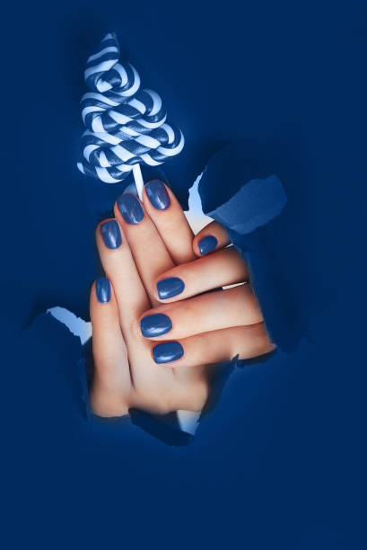 Female hands with blue nails on gray background