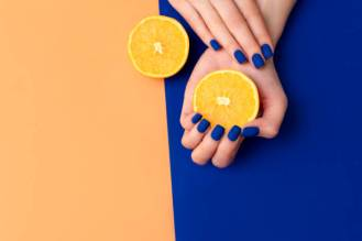 Hand with artificial manicured nails colored with blue and orange nail polish on textile background.