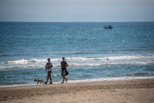 TERRACINA, ITALY - MAY 06: People walk on an empty beach about 100 km (80 miles) south of Rome during the third day of the so called phase two due to the Coronavirus (Covid-19) pandemic, on May 6, 2020 in Terracina, Italy. Italy was the first country to impose a nationwide lockdown to stem the transmission of the Coronavirus (Covid-19), and its restaurants, theaters and many other businesses remain closed. (Photo by Antonio Masiello/Getty Images)