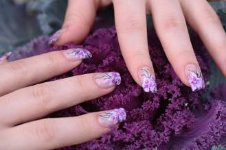 beautiful woman hand having artificial nails with pink, white and purple decoration.perfect pictures for showing the truly beauty for woman.