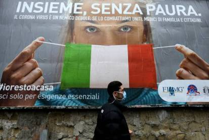 "TOPSHOT - A man walks past a large billboard raising awareness to the measures taken by the Italian government to fight against the spread of the COVID-19 (novel coronavirus) which pictures a woman wearing Italy's national flag as a facemask for protective measures and reads ""All together, without fear"", in the streets of Naples on March 22, 2020. - Italian Prime Minister, on March 21, ordered all non-essential companies and factories to close nationwide to stem a coronavirus pandemic that has killed 4,825 people in the country in a month. (Photo by Carlo Hermann / AFP) (Photo by CARLO HERMANN/AFP via Getty Images)"