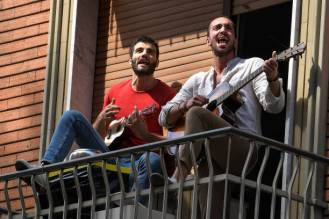 VIA TIZIANO, TURIN, ITALY - 2020/04/25: People play guitars and sing the song 'Bella Ciao' on their balcony as part of a flash mob to celebrate Liberation Day. April 25 is the Liberation Day (Festa della Liberazione) marking the Italy's liberation from nazis and fascists and the end of the Second World War (WWII) for Italy. The recurring torchlight procession and demonstration are not going to be celebrated due to the COVID19 restrictions. (Photo by Nicolò Campo/LightRocket via Getty Images)