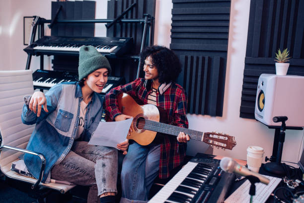 Two young musicians composing music in the studio and having fun.
