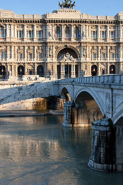 [UNVERIFIED CONTENT] The neo-renaissance building Palazzo di Giustizia, the palace of Justice, which currently hosts Italy's main law courts, situated near the river Tiber in Rome, with the bridge over the Tiber in front of the picture. The Palace, lit by the warm sunlight at dawn, is reflected in the river.