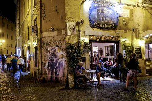 People sit outside a cafe in the district of Trastevere, in downtown Rome, on August 7, 2016. / AFP / ANDREAS SOLARO (Photo credit should read ANDREAS SOLARO/AFP via Getty Images)