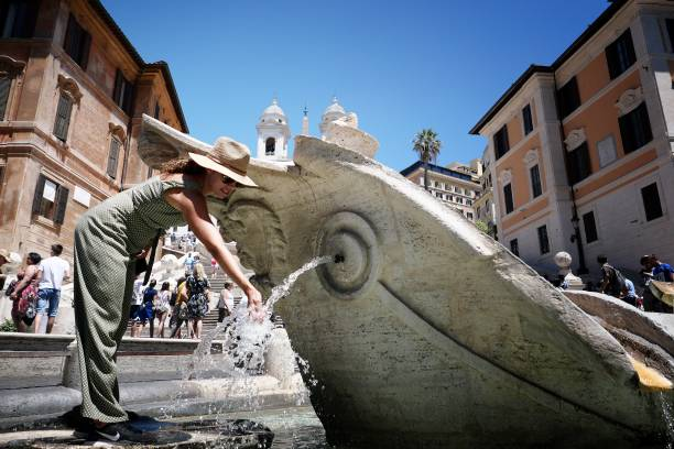 A woman refreshes at the Fontana della Barcaccia on Piazzia di Spagna in downtown Rome during an unusually early summer heatwave on June 24, 2019. - Fans flew off store shelves and public fountains offered relief from the heat as temperatures soared in Europe on June 24, with officials urging vigilance ahead of even hotter conditions forecast later in the week. Meteorologists blamed a blast of torrid air from the Sahara for the unusually early summer heatwave, which could send thermometers up to 40 degrees Celsius (104 Fahrenheit) across large swathes of the continent. (Photo by Alberto PIZZOLI / AFP) (Photo credit should read ALBERTO PIZZOLI/AFP via Getty Images)