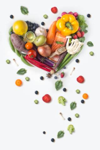 Flat lay view of heart shaped raw vegan food pile on white background.