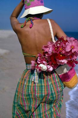 An unidentified female model walks along the beach, dressed in a crochet hat and swimsuit, and multi-colored Tartan skirt, with a crochet bag full of flowers over her shoulder, the Hamptons, New York, August 1972. This photo was taken as part of a fashion shoot for the magazine Ladies Home Journal. (Photo by Susan Wood/Getty Images)