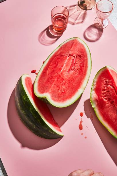 Bon Appetit - Slices of watermelon and cocktail glasses cast shadows on a sunlit pink surface. (Alex Lau/Conde Nast via Getty Images)