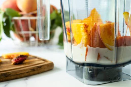 Cut fresh peaches and plant-based milk in a blender ready to make a smoothie.