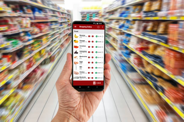 Man's hand holding a smartphone wich displays an online shopping application. In the background a supermarket lane made unrecognizable by retouching, blur and motion effect. The application layout is an original creation by the author of the image.