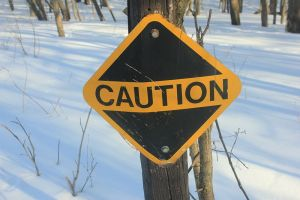 Caution sign on wooden pole in front of snowy landscape