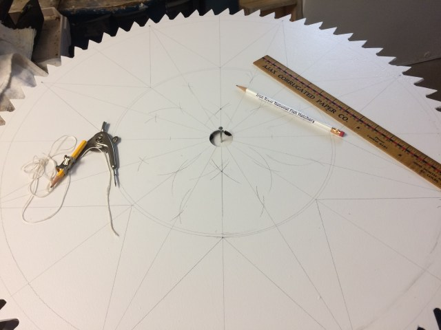 8 pointed star laid out on a sawblade, with compass and straight edge