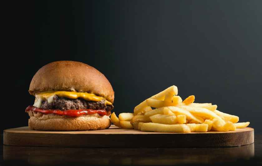 classic hamburger and french fries on wooden board